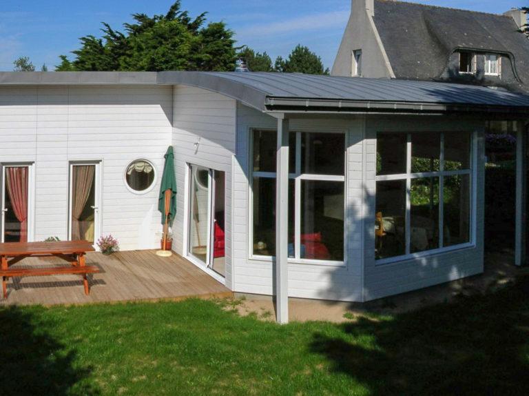 Maison ossature bois, toiture courbe, salon déplafonné.