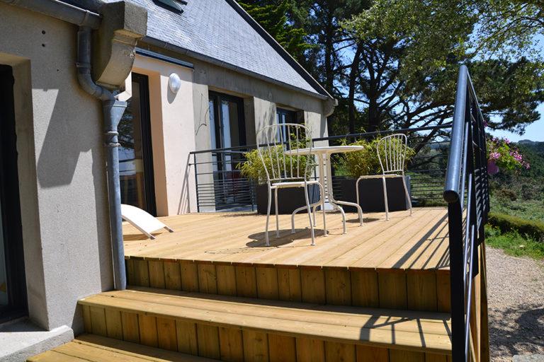 Terrasse en bois sur pilotis avec garde-corps en ferronnerie.