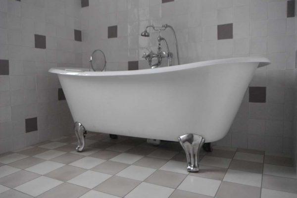 Baignoire en fonte sur pieds et carreaux de ciments.